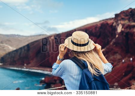 Tourist Looking At Red Beach Landscape From View Point In Akrotiri, Santorini Island, Greece. Woman
