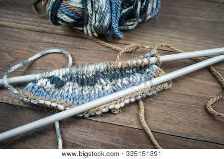 Color Thread For Knitting, Knitted Scarf, Knitting Needles On A Dark Wooden Background. Copy Space.