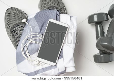 Sports Stuff And A Mock Up Mobile Phone. Gym Stuff, Mobile Phone And Blank Space For Exercise Plan O