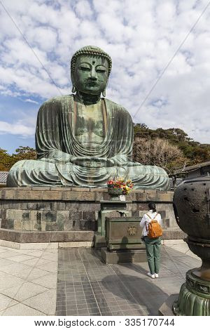 Kamakura, Japan - November 1st, 2018: A Visitor Prays In Front Of The Giant Buddha Statue At The Kot
