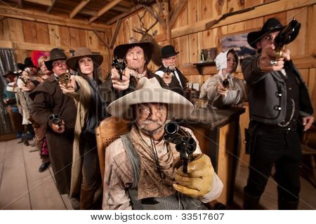 People Aiming Guns At Camera In Saloon