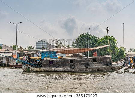 Cai Be, Mekong Delta, Vietnam - March 13, 2019: Closeup Of Old Gray Wooden Barge With Blue Outboard