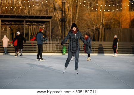 Girl Ice Skating At A Public Ice Rink. Girl Is Skating At A Public Ice Rink. Beautiful Autumn View O