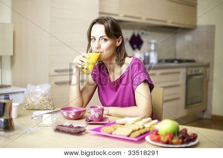 Portrait Of Female Model Drinking Orange Juice At Home During Breakfast