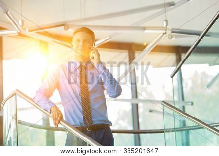 Young attrctive businessman talking on smartphone in office with lens flare