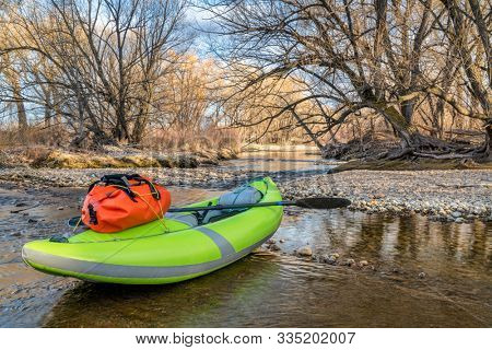 whitewater inflatable kayak with a paddle and waterproof duffel on a river  shore - Poudre River in Fort Collins, Colorado in early spring scenery and low water, water sports and recreation concept