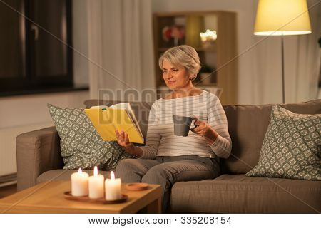 age, leisure and people concept - happy senior woman reading book and drinking coffee or tea at home in evening