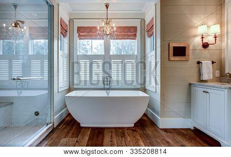 High end bathroom with large white bathtub and shiplap siding.