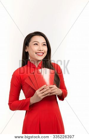 Happy Lunar New Year, Young Vietnamese Woman In Traditional Ao Dai Red Dress Holding Red Envelope Is