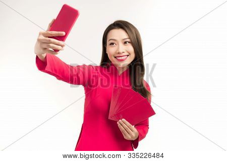 Portrait Of A Happy Young Girl Dressed In Ao Dai Taking A Selfie While Showing Red Envelope Isolated