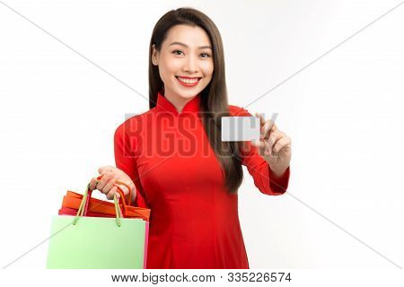Beautiful Asian Young Woman In Aodai With Shopping Bags  Holding Credit Card Over White Background