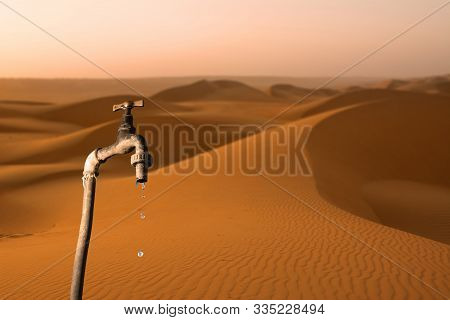 Faucet That Drips And Desert In The Background, Concept Of The Drying Up Of The Planet And Water Sca