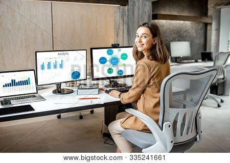 Portrait Of A Young Office Employee Working With Some Charts And Statistics On The Computers In The