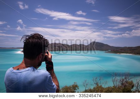 Young Man Photographing The Blue Coloured Whitehaven Beach