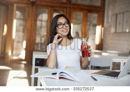 Freelance And E-learning Concept. Beautiful Girl In Glasses Holding Glass Bottle Of Juice, Taking Br
