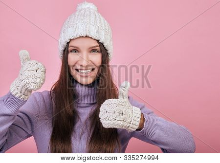 Sweetly Pretty Girl With Green Eyes In A Knitted Hat, Purple Sweater And Mittens Stands On Pink Back