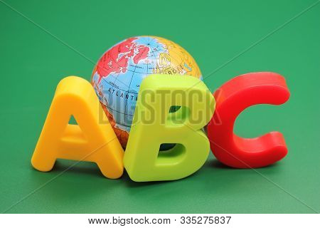 Colored Abc-letters Of The English Alphabet And Small Toy Globe On A Green Background. Learning Fore