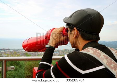 Young Man Observing Aerial City View With Binoculars From The Observation Deck