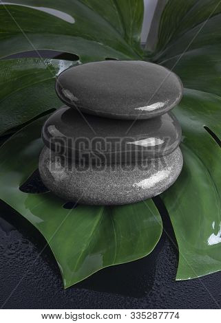 Spa Concept Of Dark Stones On The Green Leaf