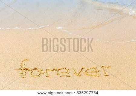 Text On A Sunny Beach. The Word Forever Written By Hand In The Sand, Washed Away By The Sea Wave. Th