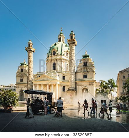 Vienna, Austria - August 20, 2019: Tourists Enjoy Views Of St. Charles Church Or Karlskirche And Buy