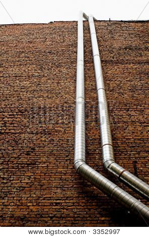 Ventilation Pipework On A Brick Building Wall