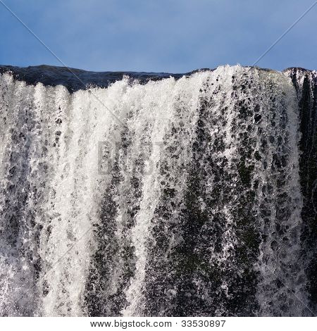 Water cascading over rock edge forming a waterfall