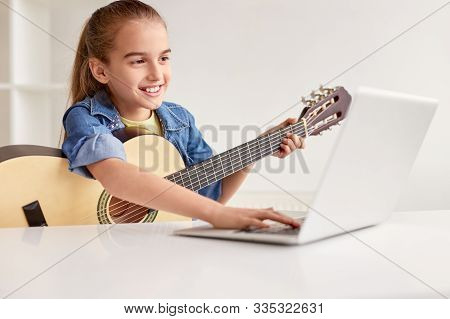 Happy Little Child In Denim Shirt Learning To Play Guitar While Watching Lessons At Laptop And Smili
