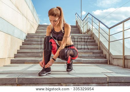 Beautiful Athletic Woman Tying Shoelaces On Sneakers, Jogging In The Morning, Stairs Background In C