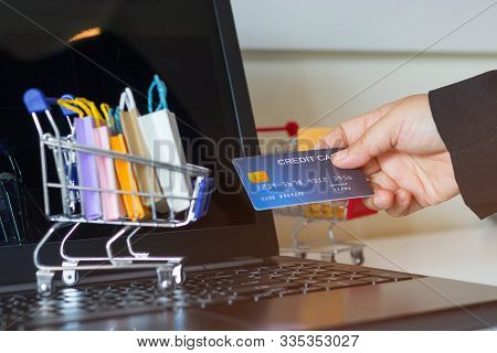 Hand Holding Mock-up Of Credit Card And Paper Shopping Bags In Trolley On Laptop Keyboard. Consumer