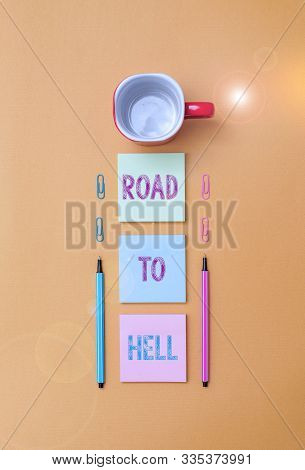 Text sign showing Road To Hell. Conceptual photo Extremely dangerous passageway Dark Ri Unsafe travel Coffee cup blank colored sticky note two ballpoints clips yolk background. poster
