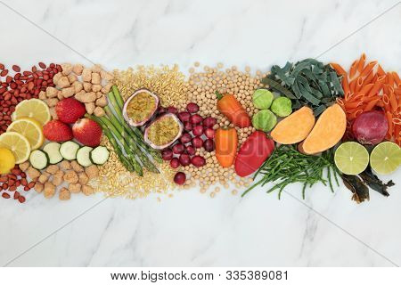 Plant based vegan food for good health with foods high in protein, vitamins, minerals, anthocyanins, antioxidants, fibre, omega 3 & smart carbs. Cruelty free food concept. Flat lay on marble.