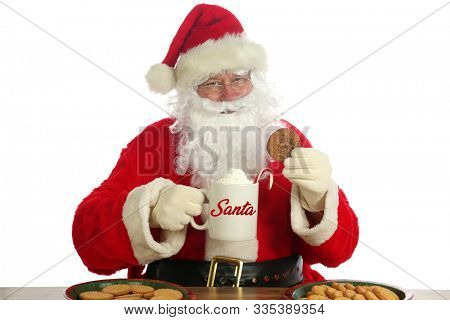 Santa Claus. Christmas Santa. Isolated on white. Room for text. Santa Claus holds a cup of Hot Coco with a Candy Cane and Whip Cream and Cookies. Santa Loves Hot Coco and Cookies on Christmas.
