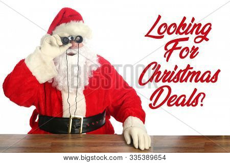 Santa Claus Christmas. Santa Claus looks through his Binoculars to see who has been Naughty or Nice. Isolated on white. Room for text. Santa is watching all year long. Looking for Christmas Deals?