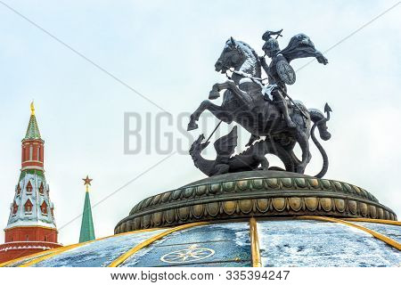 Moscow, Russia - Feb 5, 2018: Statue Of St George Against Moscow Kremlin During Snowfall. It Is A Sy