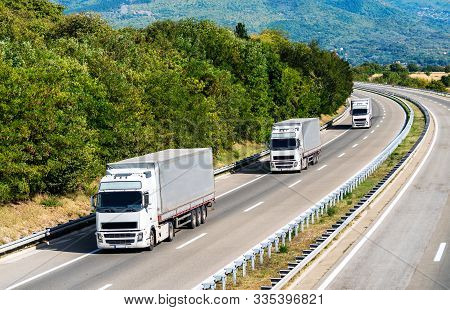 Three White Lorry Trucks In Line On A Country Highway Under A Beautiful Sky