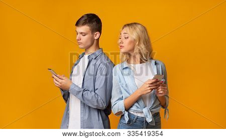 Mistrust Concept. Curious Young Girl Peeking Over Shoulder How Her Boyfriend Texting On Phone, Panor