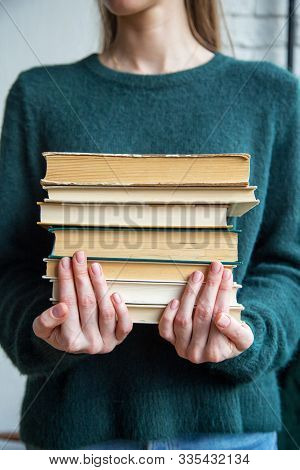 Girl Holds Stack Of Old Books. Young Student Girl Holds Secondhand Books. Concept Of School And Univ