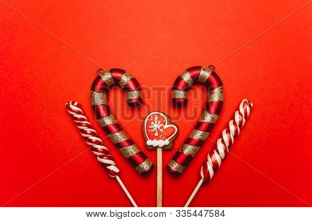 Christmas Sweets On A Red Background: Gingerbread In The Shape Of Mittens, Lollypops. Festive Mood,