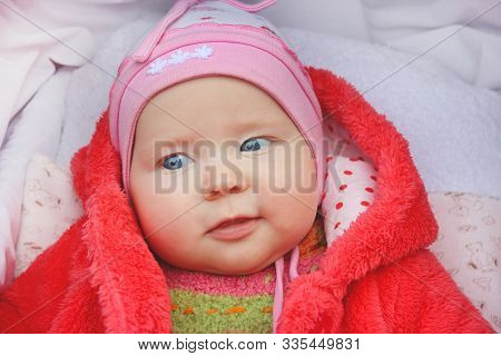 Little Baby In Red Suit Smiling In Perambulator. Happy Baby Laying In Pram. Childish Face Close Up