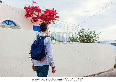 Man Traveler Walking In Akrotiri Village On Santorini Island, Greece. Tourist Admiring Architecture