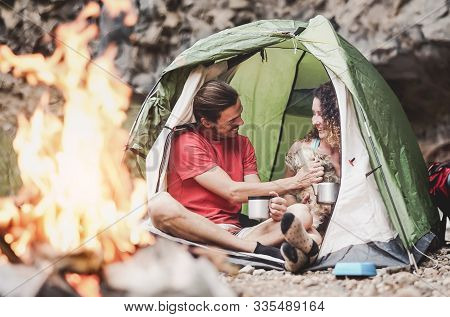 Happy trekker couple camping tent with dog next bonfire - Hipster man and woman having fun mountaineering together - Love relationship and travel lifestyle concept