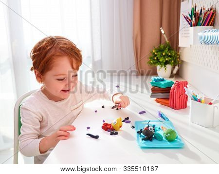 Happy Kid Is Creating The Hand Crafts From Modelling Plasticine At The Desk In The Kids Room