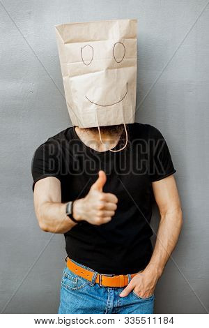 Portrait Of A Man With Paper Bag On His Head Showing Ok Sign On The Grey Background. Concept Of Face