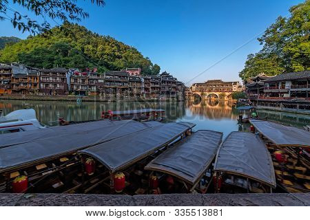 Old Historic Wooden Tourist Boats On The Riverbanks Of Tuo River, Flowing Through The Centre Of Feng