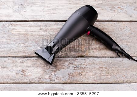 Black Hair Dryer On Wooden Background. Electric Hair Dryer On Vintage Wooden Surface.