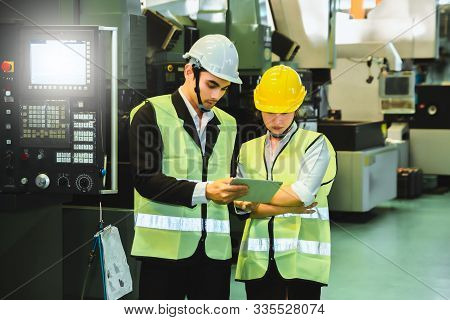 Asian Female Engineer Factory Inspection With Man Business Holding Tablet