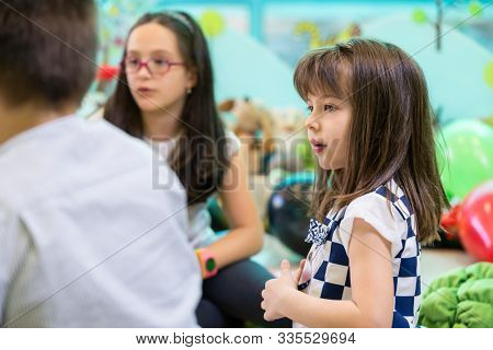 Side view of a cute and shy girl looking at her older colleagues interacting during free playtime in the classroom of a modern kindergarten