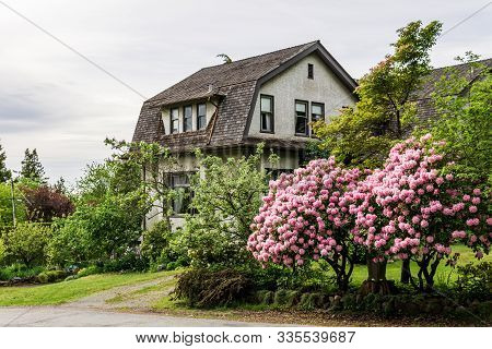 Vancouver, Canada - May 15, 2019: Beautiful House With Nicely Trimmed Green Street View.