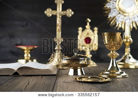 Roman Catholic Church Theme. The Cross, Holy Bible, Monstrance, Rosary And Golden Chalice On Rustic